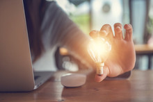 New Ideas With Innovation And Creativity Concept, Young Women Hand Holding Light Bulb While Using On Laptop.
