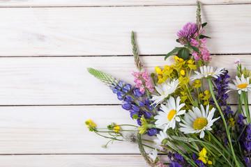 Fototapeta Wild flowers on old grunge wooden background (chamomile lupine dandelions thyme mint bells rape)