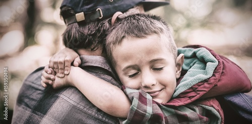 Father and son embracing in forest Wallpaper Mural