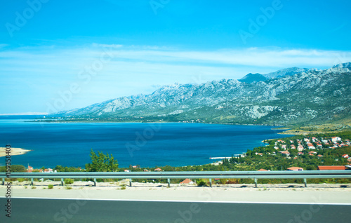 Fotografie, Obraz  Highway on the background of Velebit mountain range, small houses among green trees and azure blue sea water on a summer day