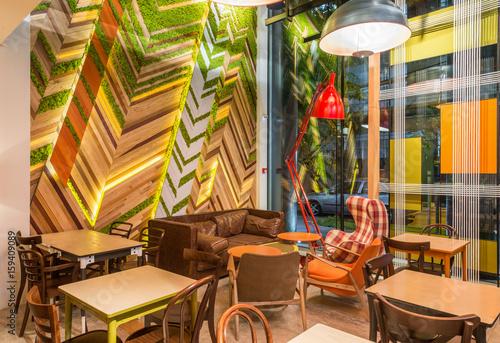 Foto auf AluDibond Gezeichnet Straßenkaffee Urban restaurant interior with green plants on the wall in the evening