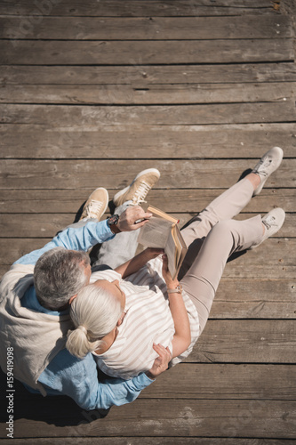 Photo above view of senior couple reading book while sitting on wooden pavement