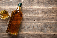 Bottle And Glass Of Whiskey On Wooden Boards