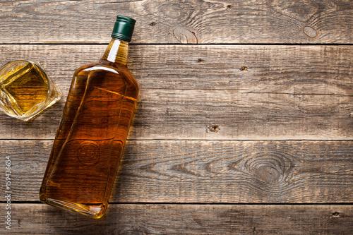Obraz na płótnie Bottle and glass of whiskey on wooden boards