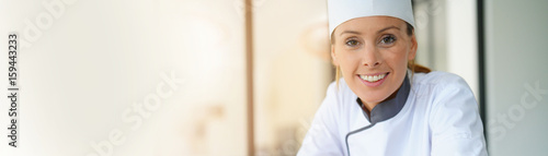 Fototapeta Portrait of pastry chef standing by raspberry cake, template obraz