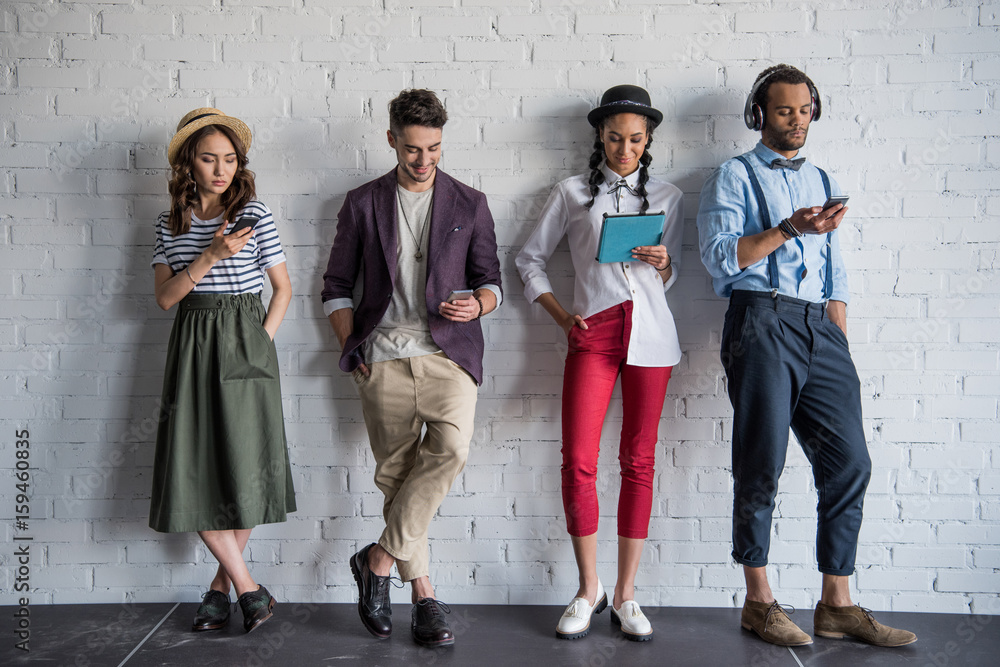 Fototapeta young stylish friends using digital devices while standing near brick wall