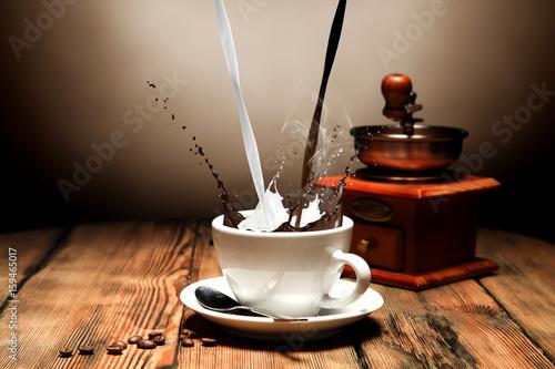 nalewanie-kawy-z-mlekiem-do-filizanki-w-tle-mlynek