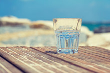 Glass Of Water On Wooden Table In The Beach