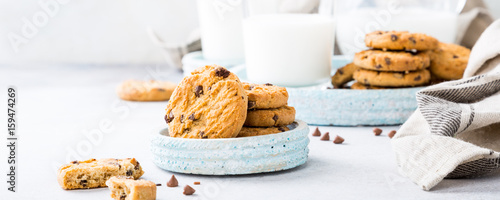 Fotobehang Koekjes Chocolate chip cookies on blue stone plate with glass of milk on light gray background. Selective focus. Copy space.