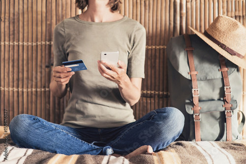 Young woman on vacations using smartphone and credit card. Online shopping and travel concept