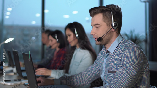 Fototapeta Young handsome men in checked shirt and headset working in call center in modern worldwide office he talking and looking on screen of desktop computer obraz