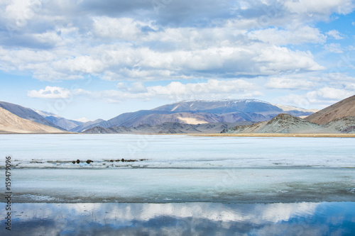 Papiers peints Alpes panoramic view of lake with snow-covered mountains at cloudy day
