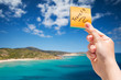 """Woman hand holding a sticky notes with the word """"travel"""" in background a beautiful seascape location - Conceptual image to suggest a vacation or a type of vacation"""