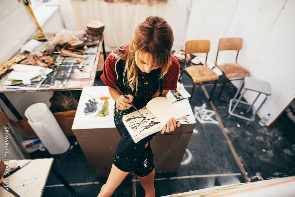 Fototapety, obrazy: Female artist drawing pictures in her workshop