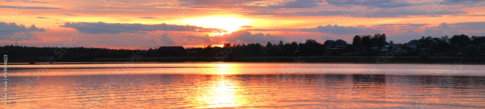 Fototapeta Panorama of the sunset overlooking the lake and the house and trees on the opposite coast.