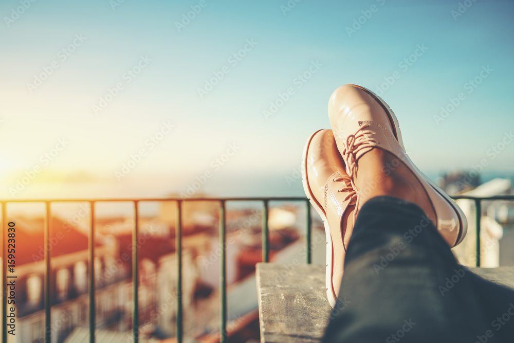 Fotografie, Obraz Female feet with glossy pale pink shoes relaxing on wooden table and touristic e