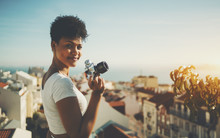 Curly Young Brazilian Lady Half Turned Towards Camera And Smiling While Standing On High Observation Point In Lisbon City And Holding Vintage Film Camera With Copy Space For Logo, Message Or Advert