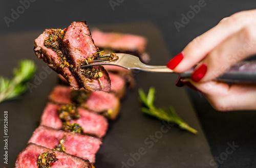 Valokuva  Young woman eating new york strip porterhouse steak meat