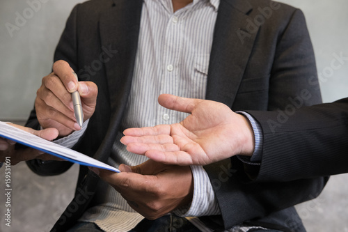 Fototapety, obrazy: Businessman and lawyer negotiating a contract, they are pointing on a document and discussing together in a meeting. business colleagues working at office