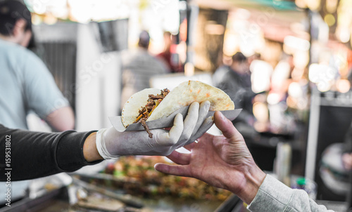 Tablou Canvas Chef handing a taco to a foodie at a street food market