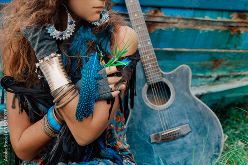 attractive gypsy girl close up portrait with a guitar leaning against the boat a Wallpaper Mural