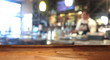 Empty wooden table top with blurred bar on background