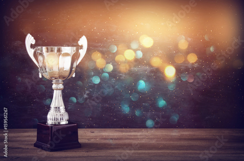 low key image of trophy over wooden table and dark background Wallpaper Mural