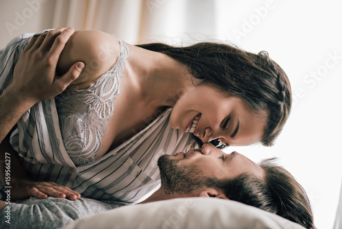 Close Up View Of Passionate Young Couple In Love Lying On Bed And Hugging