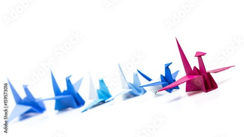 Leadership concept with red origami bird leading among blue.
