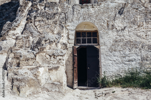 Fototapety, obrazy: Ancient wooden door in the white chalky mountain, the entrance to the hollowed temple inside