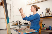 Mid Adult Woman Photographing Oil Painting In Artist's Studio