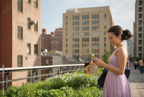 Foto Murales Mid adult women using digital tablet in High Line Park, New York City
