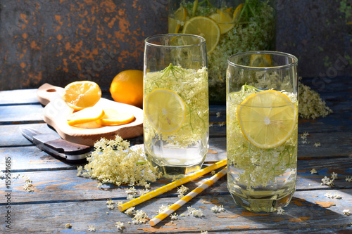 Elderberry flowers and lemon drink. Refreshment healthy elder juice. Glass of elderflower lemonade on wooden rustic board. Alternative medicine and therapy