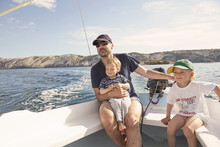 Mature Man Steering Motor Boat With Sons, Lopar, Rab Island, Croatia
