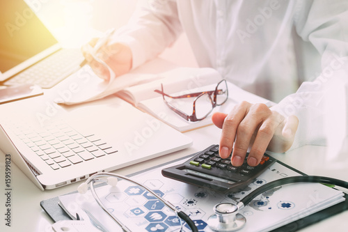 Obraz Healthcare costs and fees concept.Hand of smart doctor used a calculator for medical costs in modern hospital - fototapety do salonu