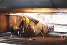 Welder Welding Beneath Boat In Shipyard Workshop