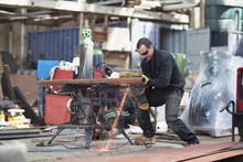 Workers Cutting Pipes In Shipyard Workshop