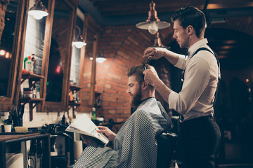 Fototapeta Do fryzjera Low angle profile view of red bearded stylish barber shop client, which is getting his perfect haircut from a classy dressed stylist, reading the magazine and waiting for result