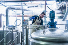 Young Man In Brewery Wearing Apron And Protective Gloves Testing Beer In Tank