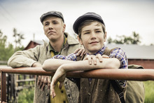 Man And Boy Wearing Flat Caps Leaning Against Farm Gate Looking Away Smiling