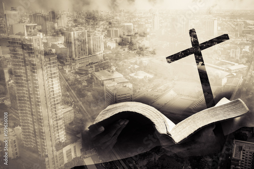 Fotografie, Obraz  mixed media of cross and city and hand hold bible