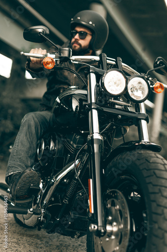 Biker in helmet and his style motorcycle on a city streets Canvas Print