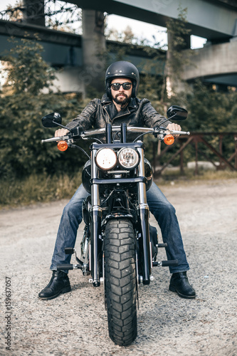Photo  Handsome rider guy with beard in black biker jacket, sunglasses on classic style cafe racer motorcycle at sunset