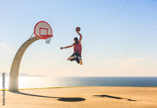 Photo  Basketball Player scoring an amazing slam dunk outdoors.