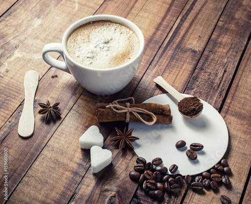 Spoed Foto op Canvas Chocolade Coffee cup, cinnamon sticks, coffee beans, anise, sugar, spoon and coasters on vintage wooden kitchen table background.