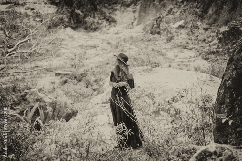 Photo beautiful woman in black dress and hat posing at stone wall background