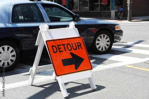 Fotografie, Obraz  detour sign on road in front of police car