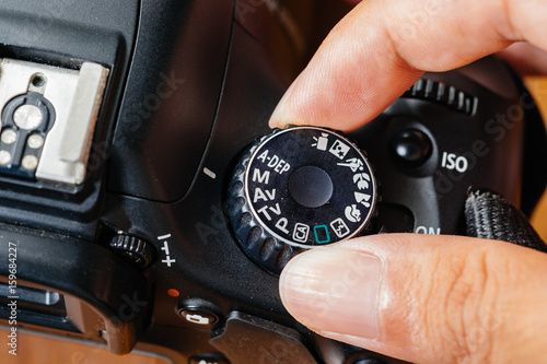 Fotomural  Manual dial mode on dslr camera with fingers on the dial