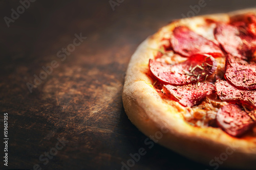 Photo sur Toile Pizzeria Pizza with pepperoni and salami on a rustic wooden table.