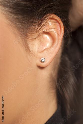 Obraz na plátně Closeup female ear with a small luxurious earring
